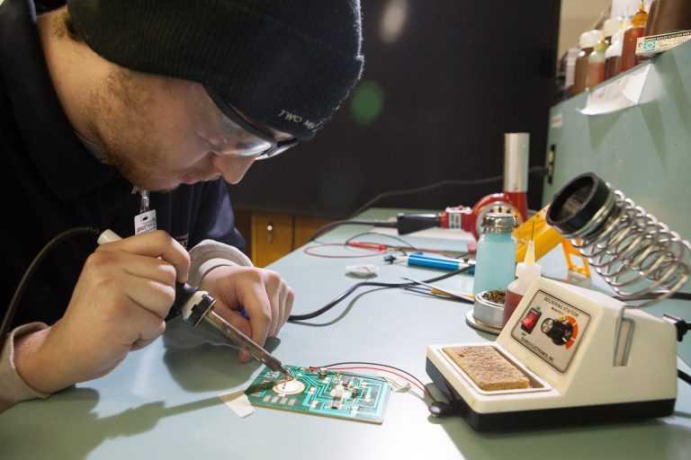 Avionics Technician Student Soldering Circuit board