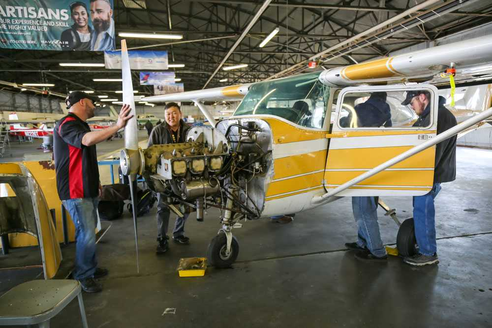 Spartan College students in class - working on yellow airplane