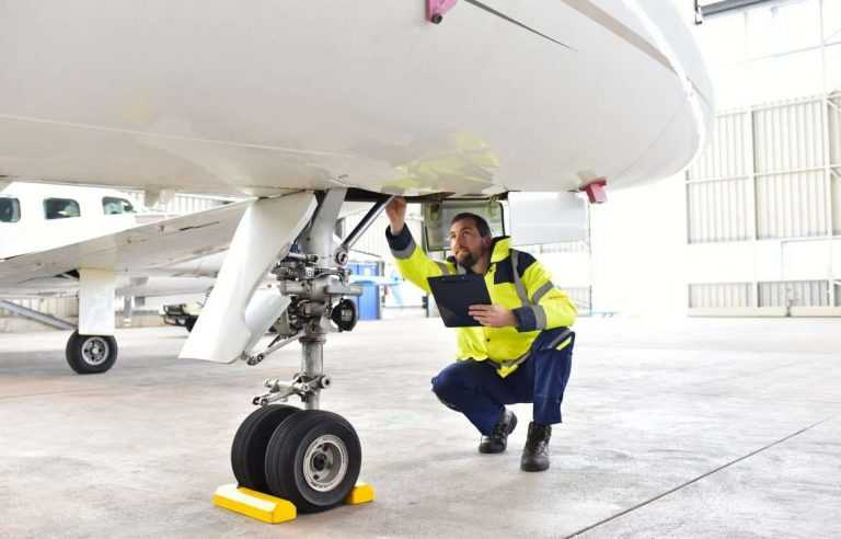 Man inspecting front wheel of airplane