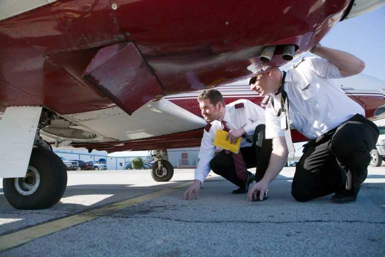 Spartan Students Looking Under Plane