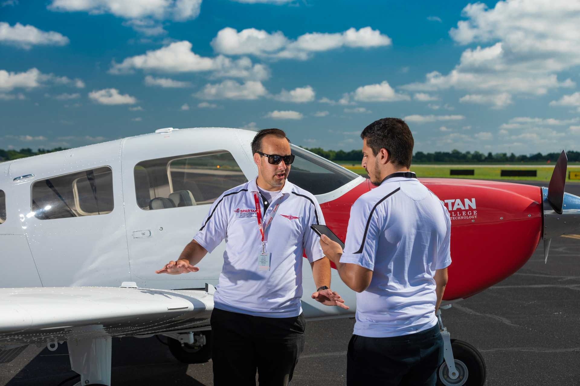 flight instructor with student in front of plane