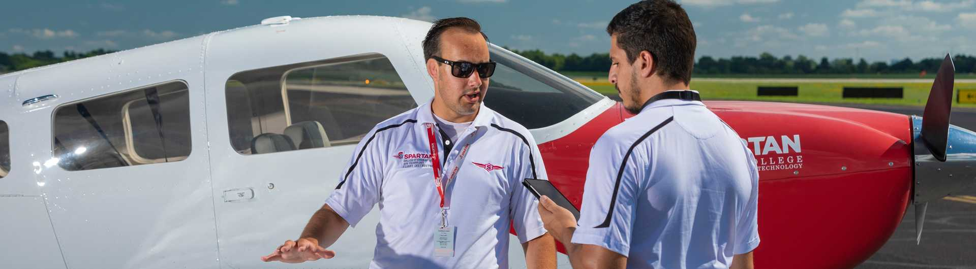 Spartan College flight instructor with student in front of plane horizontal