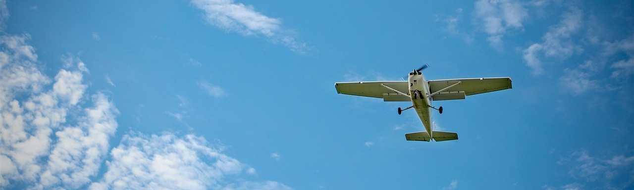 Plane in Flight behind blue sky